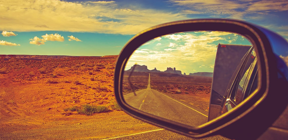 A car's side mirror looks back on the road while travelling with the desert in the background