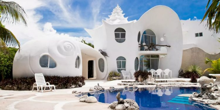 A white seashell inspired home comes is two stories high with an outdoor patio and swimming pool