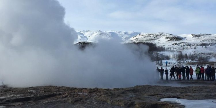 Tourists are photographing a geyser that recently ejected a column of hot water and steam