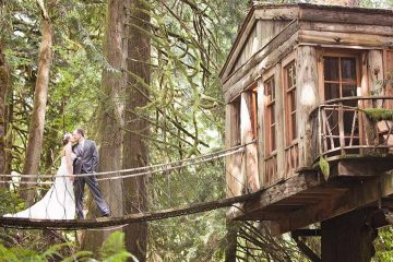 A bride and a groom are kissing on a bridge that attaches to a tree house in the woods