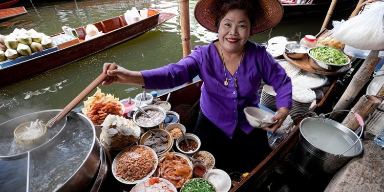 A woman is preparing traditional cuisine of her culture. She holds a spoonful of rice noodles.