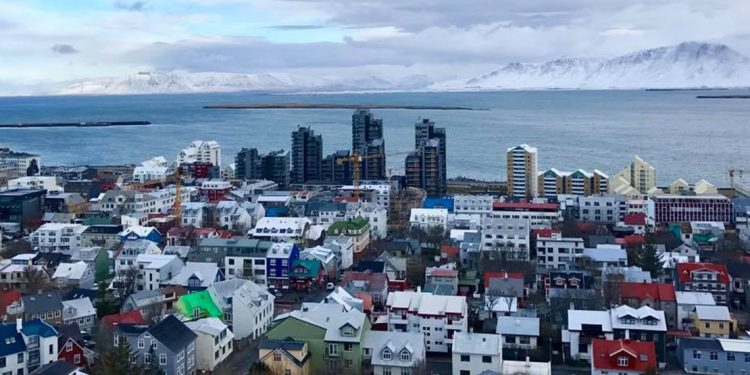 A panoramic view of the city of Reykjavik with the ocean and mountains in the background
