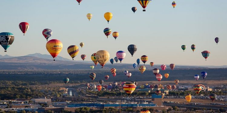 Numerous colorful hot air balloons fly above a city