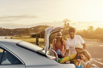 A family of four is packing their luggage in the car's back trunk
