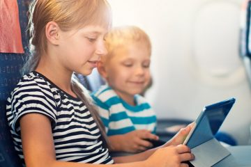 Two kids playing with a tablet in their airplane seats