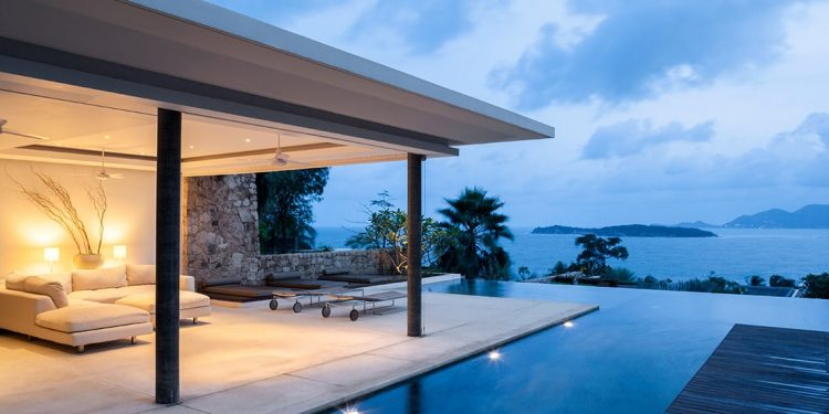 A luxurious hotel includes an outdoor sofa with a patio and private pool with a view of the ocean