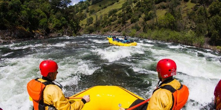 Two individuals watch a group of people white water rafting