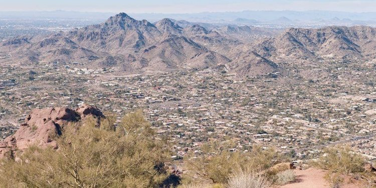 A photo of an Arizona city is taken from a small mountain in Piestewa Park during the day