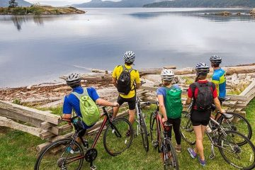 A family of bikers take a break to look straight at a body of water