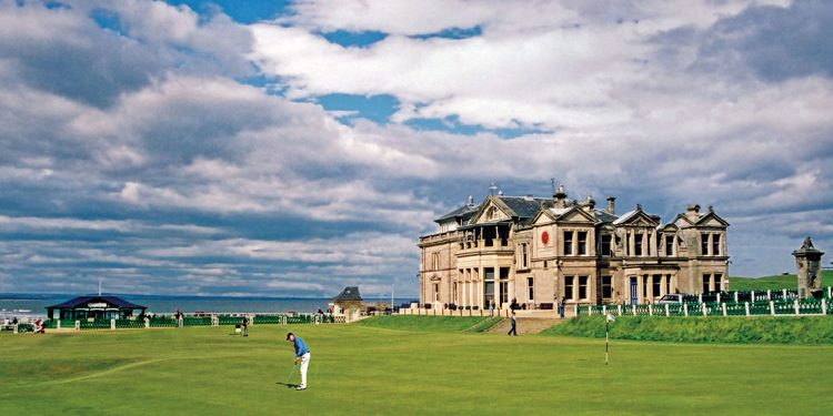 The famous St. Andrew's building in Scotland is in the background while a golfer is teeing off on the golf course