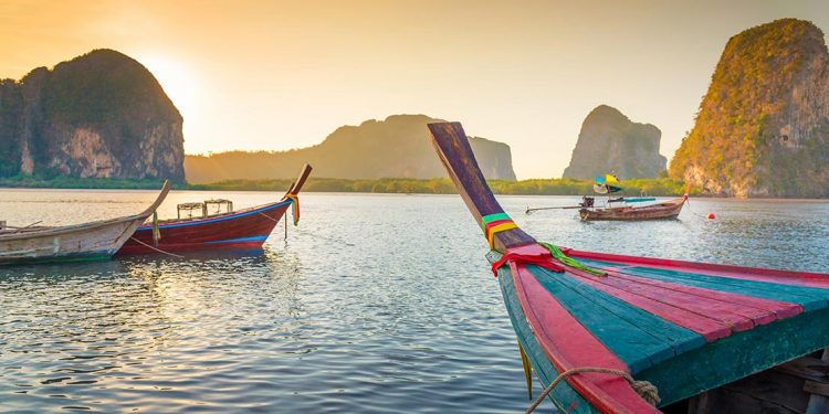 Three boats are drifting along the stunning Thailand waters during the sunset