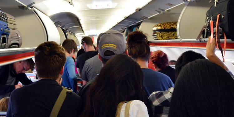 A group of people is preparing to get off of their plane ride
