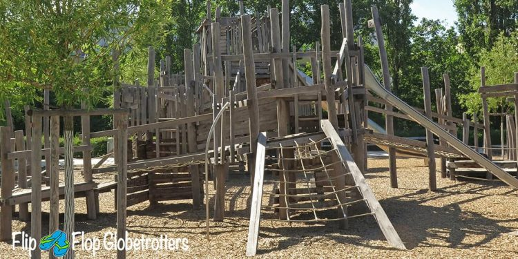 Wooden climbing structure with rope ladder leading up and a metal slide on the side.