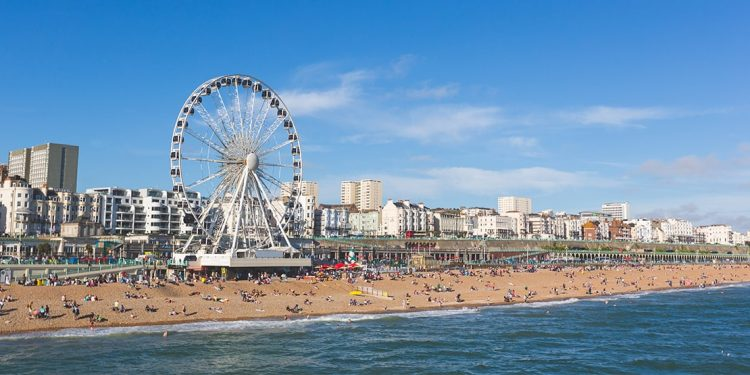 Ferris wheel on edge of beach where many people are sunbathing. White buildings in background up on raised ledge.