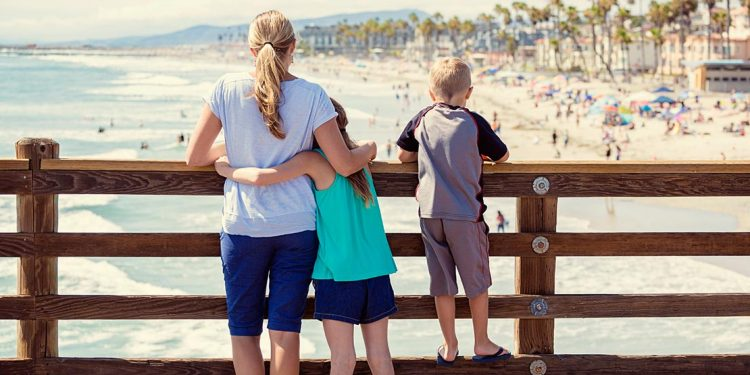 Daughter has arms wrapped around her mom's waist as they look out at a beach from up on a boardwalk. Son is standing on bottom rung of fence beside them.