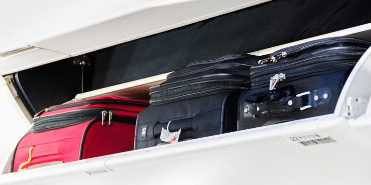 Carry on luggage in the overhead bin of an aircraft