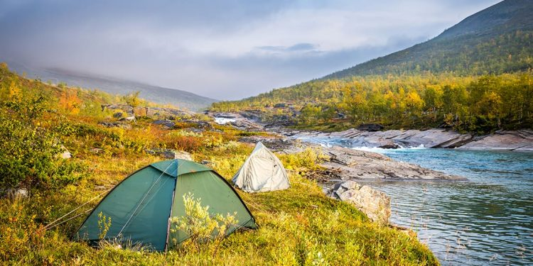 Two tents pitched at edge of river among green shrubbery.
