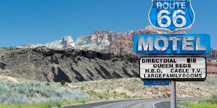 Blue roadside sign for Route 66 motel in front of curve of road with mountain rising up on left side.