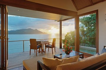 Deck of a villa with couch, glass coffee table, small table and chairs looking out onto the ocean.