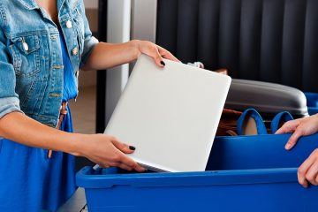 Woman stands with laptop in her hand and is about to place it into a blue bucket along the security conveyor belt. Man on other side of belt has bucket in his hands.