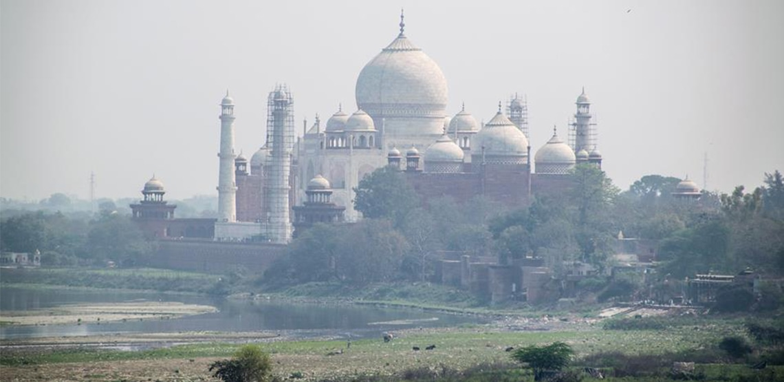 Back side of Taj Mahal with shallow water and stony ground.
