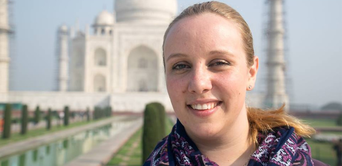 Smiling face of woman out front of Taj Mahal.