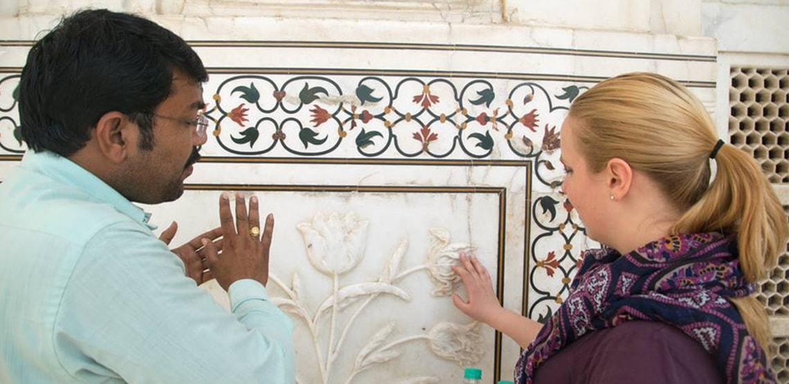 Indian man speaking with young woman in front of intricate gemstone designs on wall.