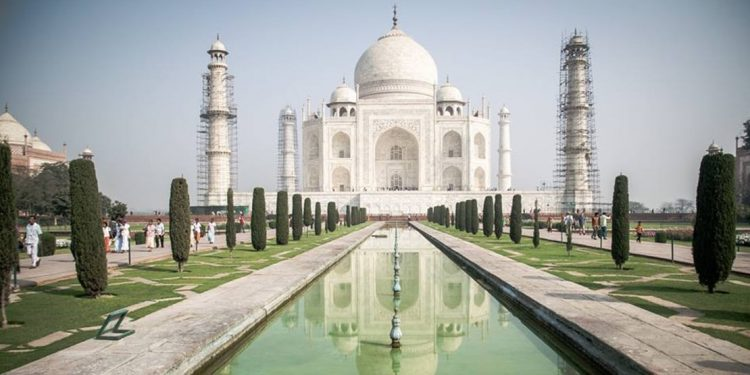 A view from the rectangular pool in front of building. Reflection of Taj Mahal is visible in the water. There are tall, carefully groomed trees on either side of pool.