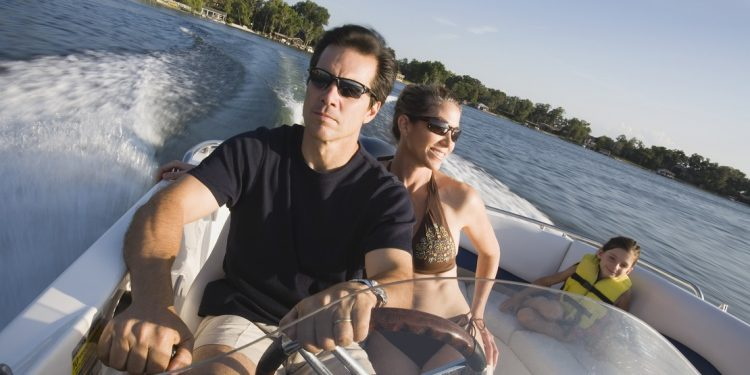 Middle aged man driving speed boat with wife in bikini seated to his left and child wearing yellow life jacket on set behind them.