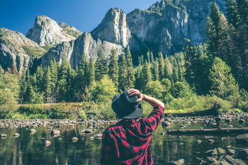 Woman in red and black plaid shirt with grey hat standing with her back to camera, facing water dotted with rocks. Trees rise up across water with grey mountain peaks.