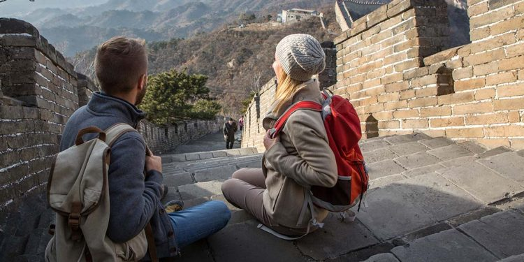 A man and woman sitting on steps of Great Wall of China.