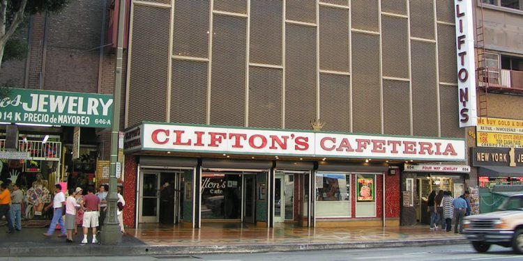 Outside of restaurant with white sign and red lettering. Brown exterior extending upwards.