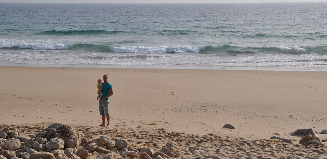 Man holding toddler on a beach in front of waves. Rocks in front of him.