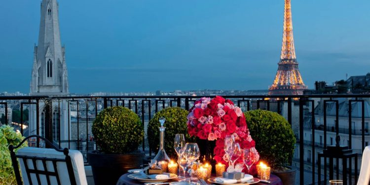 Balcony with candlelit dinner on small table with Eiffel Tower and church spire visible over railing.
