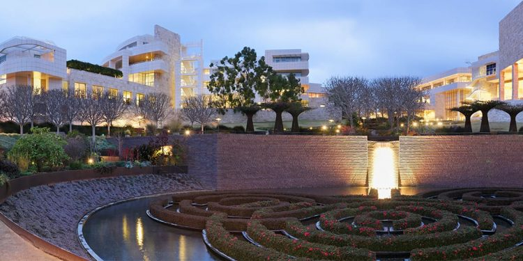 Spiral of plants on water with brick wall in behind. Surrounded by trees. White walls of the Getty Center visible in the background.