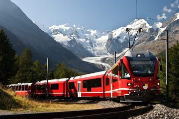 Red train coming around a corner with white peaked mountains in the background.