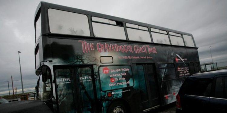 "Black doubledecker bus with ""The Gravedigger Ghost Tour"" on the side in red lettering."