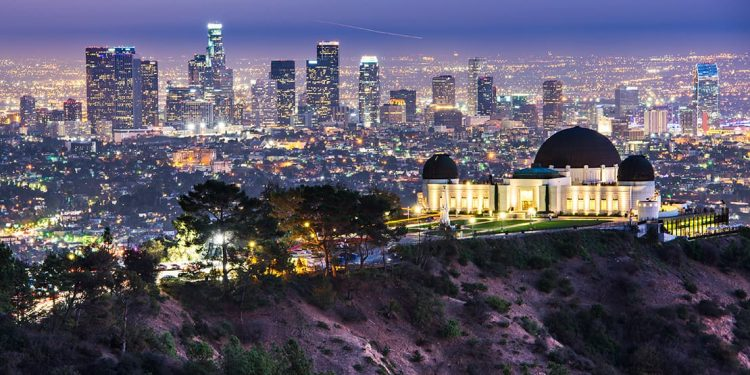 Dome-shaped building on edge of a cliff with LA in the background. Skyscrapers and houses lit up.