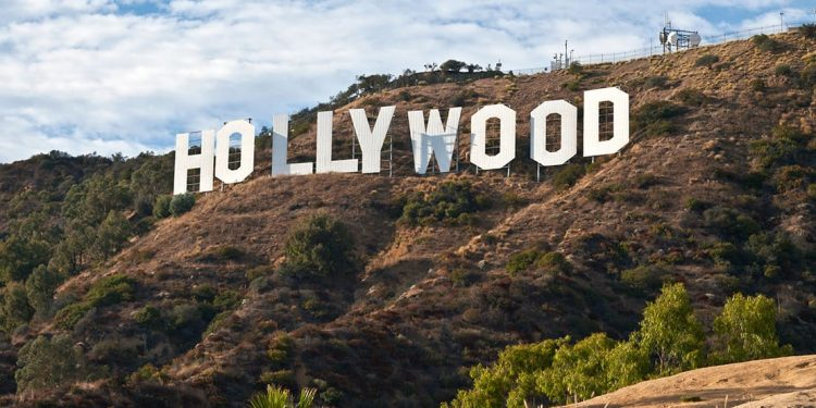 White letters of the Hollywood sign set on a green and white hill.