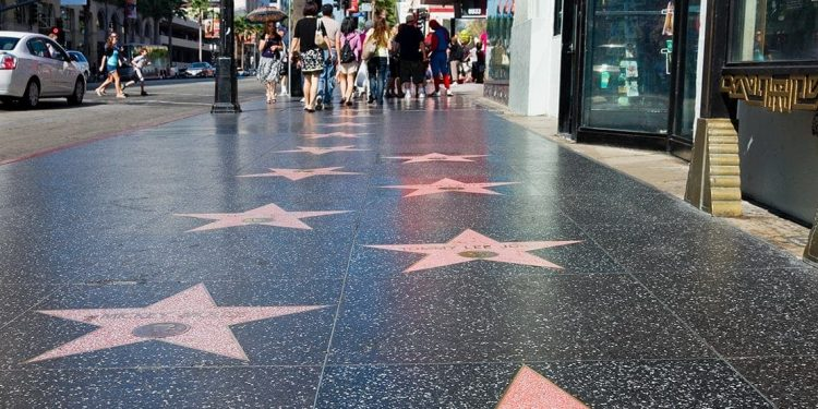 Pink stars inset in the grey sidewalk with names of famous actors. People walking further down the sidewalk.