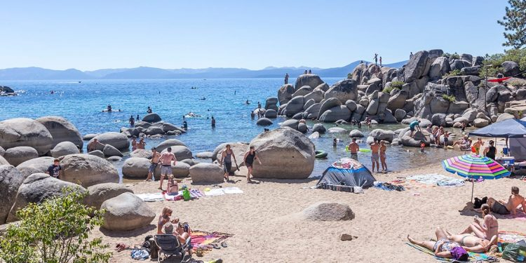 People sunbathing on the beach with giant boulders in and around the water.