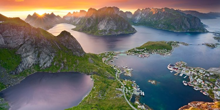 Mountainous, rocky islands with road winding along their edge and small cottages next to the water.