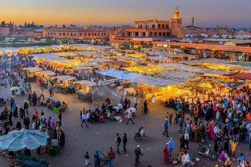 A market in a city square. White roofed tends with yellow lights underneath them. People milling about. City buildings in the background.
