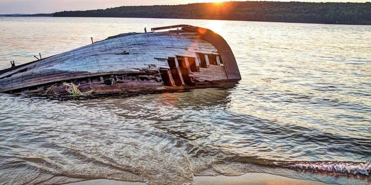 A shipwreck sticking out of the lake, its hull missing many boards.