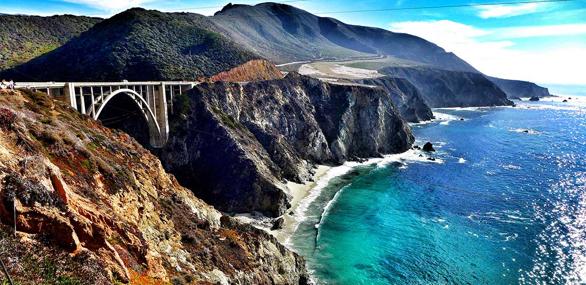 Bridge leading from one cliff face to another with ocean down below.