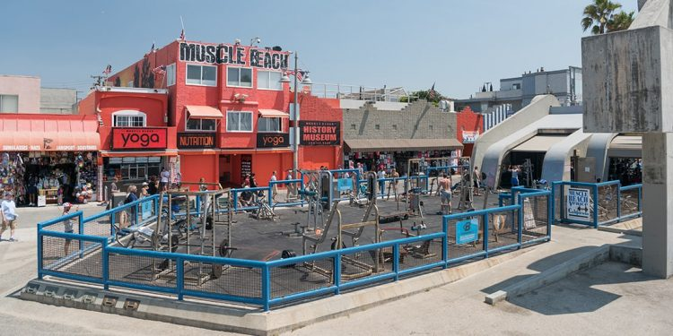 Red building with Muscle Beach painted on top of it. Blue fenced off area with fitness equipment.