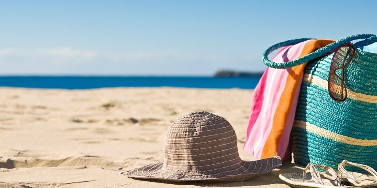 Sun hat, beach bag with towel and sunglasses hanging off of it, and sandals on the beach.