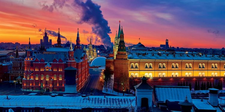 Russian-inspired building with towers and spires, smokestacks spewing smoke in the background against a red sky.