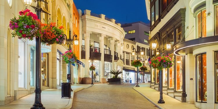 Cobblestone street with white sidewalks and metal streetlamps. Shop fronts are all white stucco.