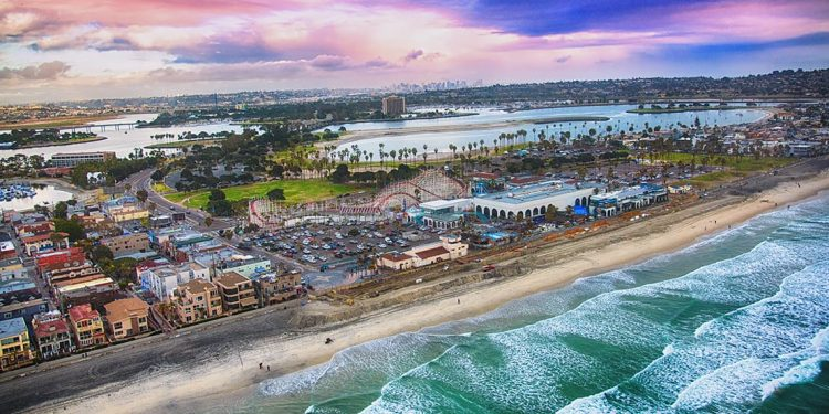 Coast of San Diego with strip of beach running along the ocean. Beach houses in grid neighborhood and roller coaster. Lakes in the distance.